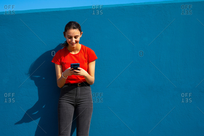 Woman dressed in red using the mobile on a blue background. concept of using the mobile. blue background.