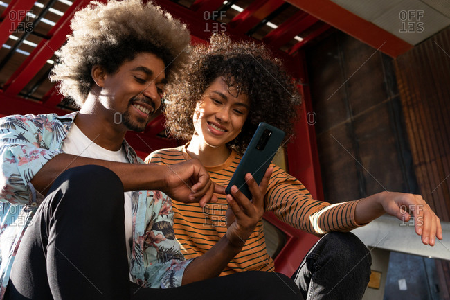From below of smiling diverse couple of friends with afro hairstyle watching cellphone under ceiling in back lit