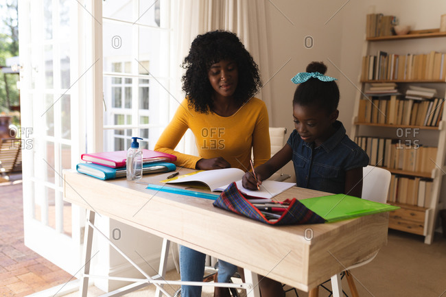 African American mother helping daughter with homework while sitting on chairs at home.