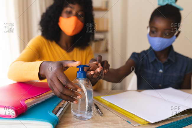 African American mother wearing face mask sanitizing hands of her daughter wearing face mask at home..