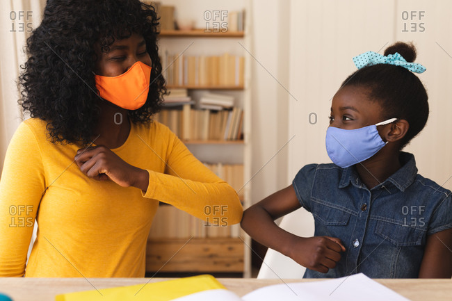 African American mother and daughter wearing face mask greeting each other by touching elbows at home..