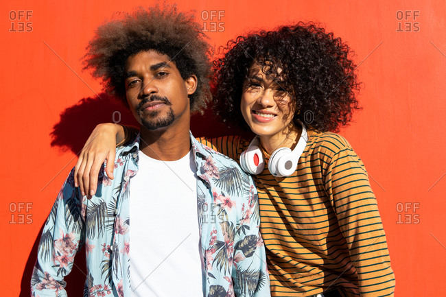 Stylish african american male with afro hairstyle standing near cheerful female friend on street looking at camera
