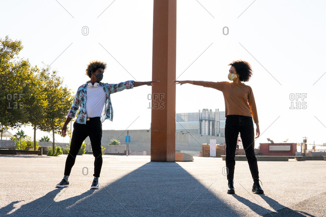 Anonymous trendy black man in mask with afro hairstyle reaching arm to female partner on street while looking at each other during quarantine period