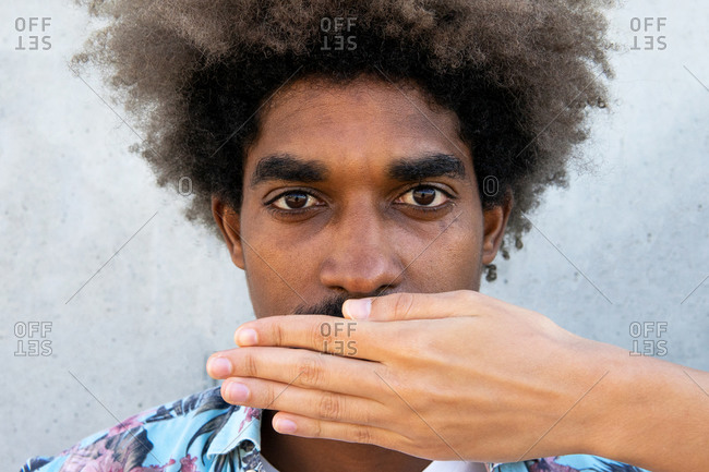Anonymous african american male friend covering face of young attentive male with afro hairstyle near cement wall while looking at camera