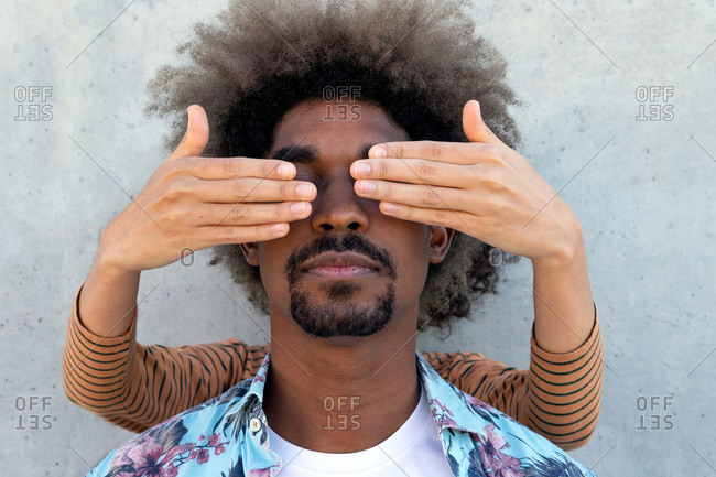 Anonymous friend covering eyes of stylish ethnic male with afro hairstyle near concrete wall