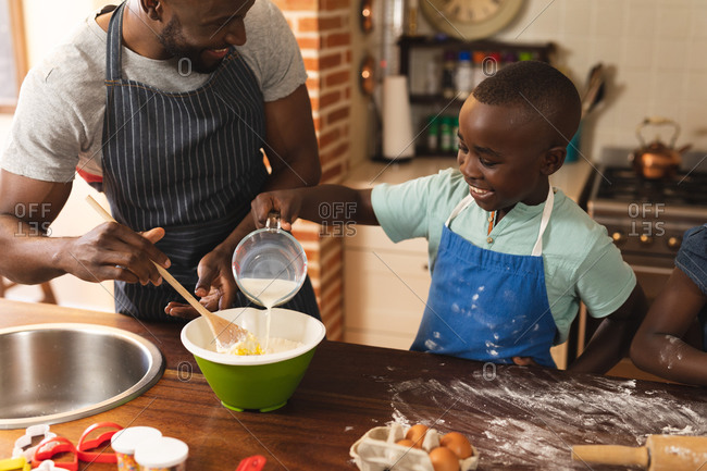 African American father and son wearing apron baking in the kitchen at home.