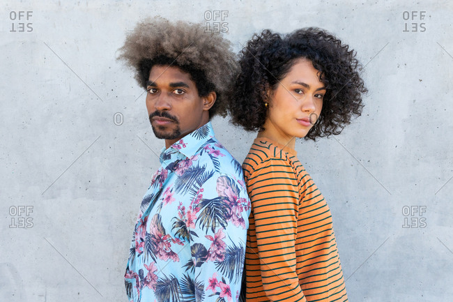 Side view of multiracial couple of partners in trendy apparel with afro hairstyle looking at camera near concrete wall