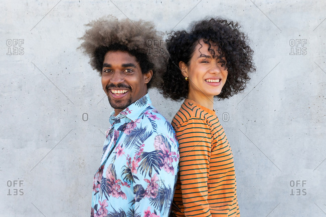Side view of cheerful multiracial couple of partners in trendy apparel with afro hairstyle looking at camera near concrete wall