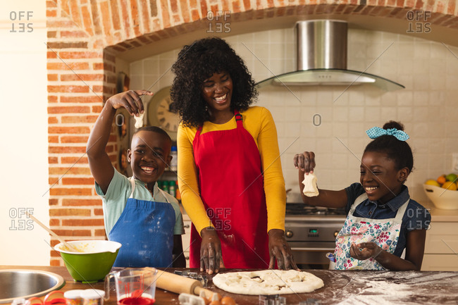 African American mother, son and daughter baking together and holding pieces of dough in the kitchen at home.