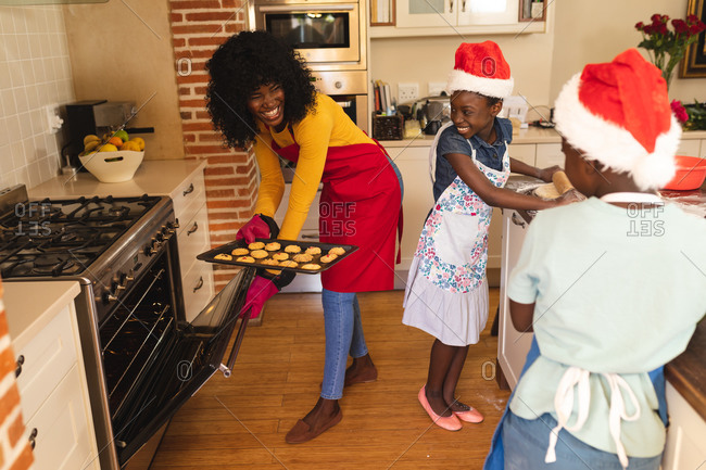 African American mother wearing apron holding baked cookies and daughter and son wearing Santa hat baking in the kitchen at home.