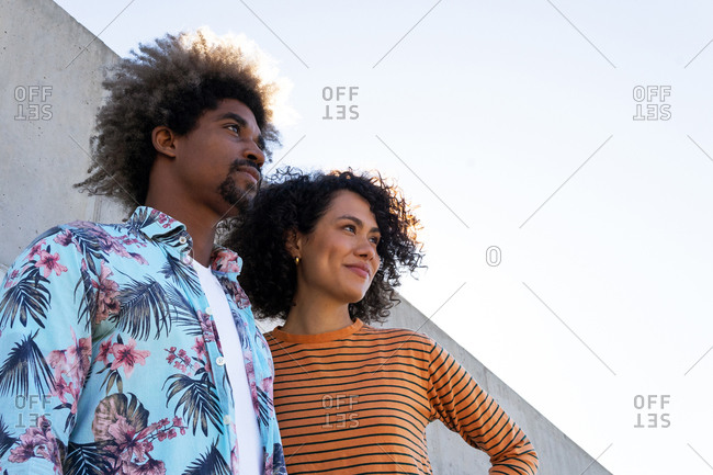 Side view of multiracial couple of partners in trendy apparel with afro hairstyle looking away near concrete wall