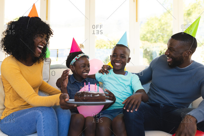 African American family wearing party hats with cake celebrating birthday sitting on the couch in the living room at home..