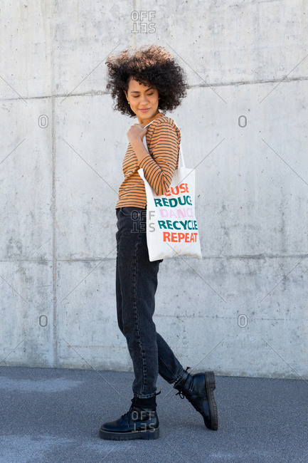 Side view of stylish young ethnic lady with curly hair in casual clothes carrying eco friendly cotton bag while standing on street