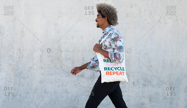 Side view of stylish young ethnic man with afro hair in casual clothes carrying eco friendly cotton bag while standing on street