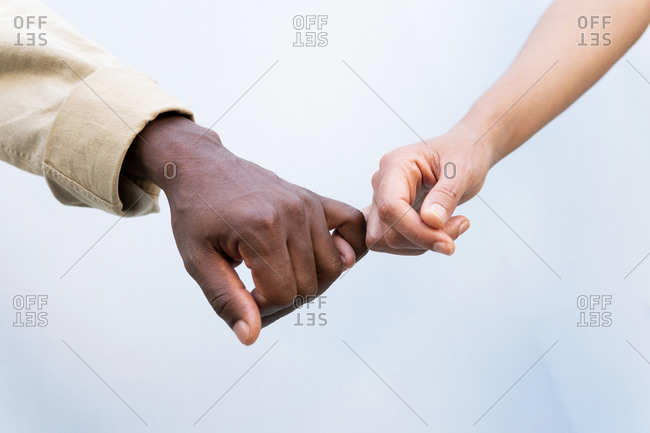 Crop unrecognizable diverse mam and woman holding hands with pinky grip against white background