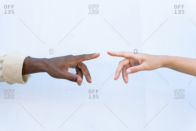 Crop unrecognizable diverse man and woman touching index fingers against white background