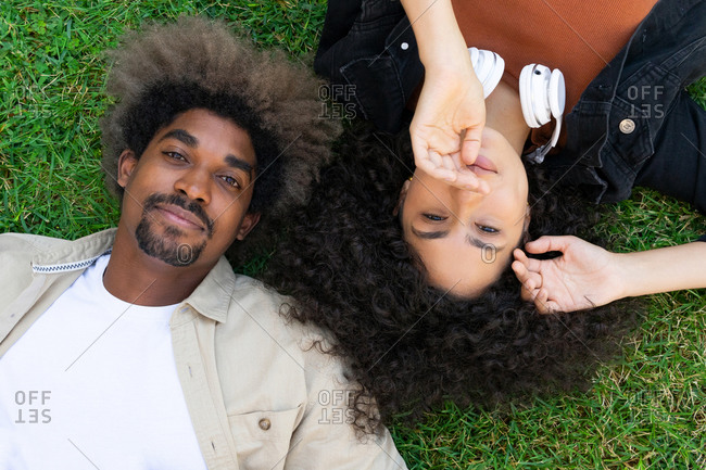 Top view of happy young black couple with afro hair lying on grass in park head to head and looking at camera