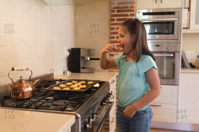 Caucasian girl standing in a kitchen and eating cookies from baking sheet.