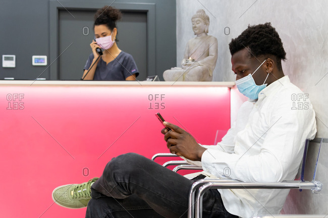 Side view of male patient in mask sitting near reception desk in modern clinic and waiting for appointment while browsing smartphone