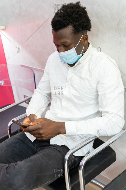 Male patient in mask sitting near reception desk in modern clinic and waiting for appointment while browsing smartphone
