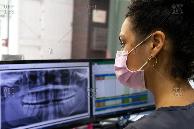 Side view of black female doctor in medical mask examining x ray on monitor of computer while working in modern dental clinic