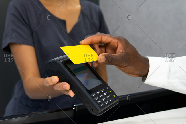 Cropped unrecognizable african american female manager in medical mask receiving payment via pos terminal and plastic card from crop male patient in modern clinic