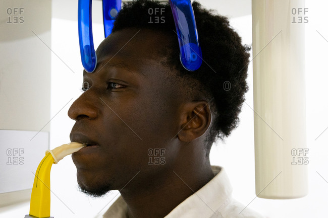 Back view of unrecognizable dentist taking x ray of teeth of black male patient sitting in medical room in modern clinic