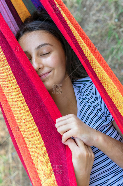 Female lying and swinging in hammock in green garden on sunny day while having sun and closed eyes