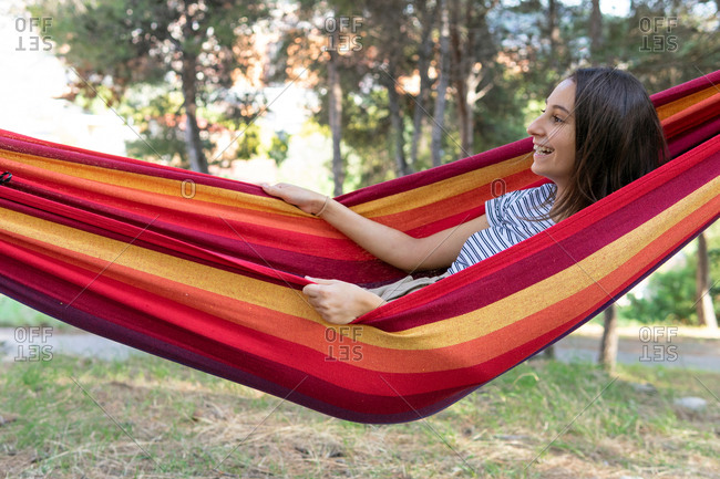 Side view of delighted female lying and swinging in hammock in green garden on sunny day while having sun and looking away