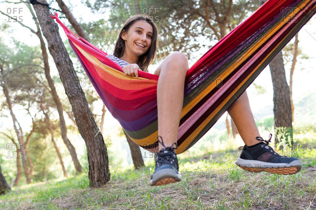 Low angle of young glad female sitting in hammock hanging between trees in garden while enjoying summer and looking away