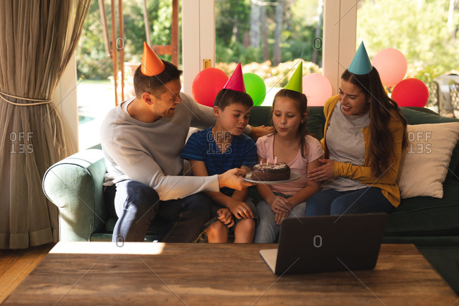 Caucasian family spending time at home together celebrating a birthday, wearing party hats and blowing candles.