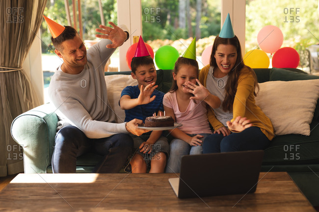 Caucasian family making a video call using a laptop at home together while celebrating a birthday wearing party hats.