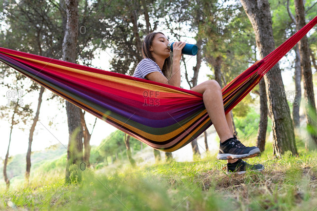 Low angle side view of thirsty female sitting in hanging hammock in park and enjoying fresh water from bottle on summer day