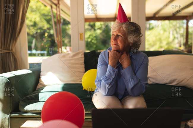 Senior caucasian woman spending time at home celebrating a birthday, wearing party hat and using laptop.