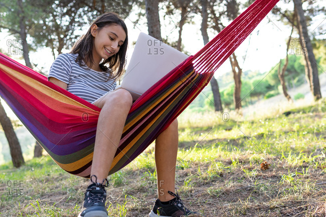 Side view of delighted female freelancer lying in hammock and typing on netbook while working on startup project