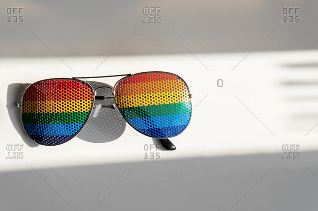 Top view of sunglasses with lenses with lgbt flag placed on white table illuminated by sunlight