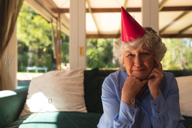 Portrait of senior caucasian woman spending time at home celebrating a birthday, wearing party hat and looking at camera.