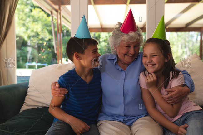 Senior caucasian woman spending time at home celebrating a birthday with her grandchildren, wearing party hats and smiling.