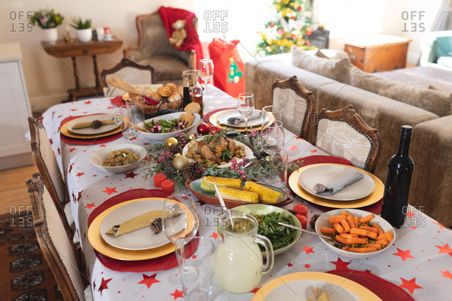 Decorated table during Christmas time, with many dishes, bottle of wine and juice lying on a table.