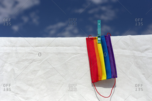 Protective mask with picture of lgbt rainbow flag attached with clothespin to thread on sunny day in backyard on background of white bed sheet