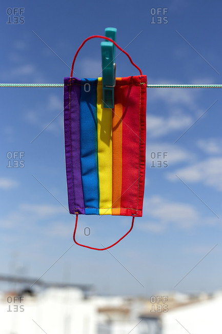 Protective mask with picture of lgbt rainbow flag attached with clothespin to thread on sunny day in backyard