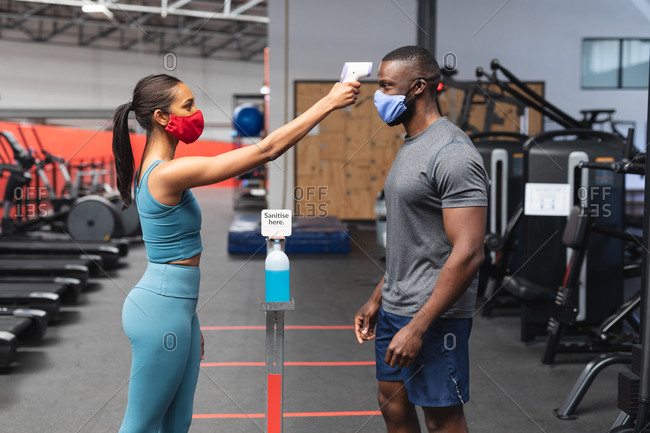 Fit caucasian woman wearing face mask checking temperature of fit African American man wearing face mask in the gym.