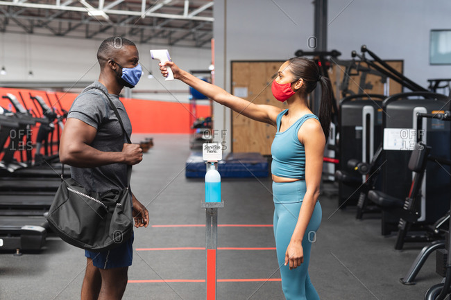 Fit caucasian woman wearing face mask checking temperature of fit African American man with gym bag in the gym.