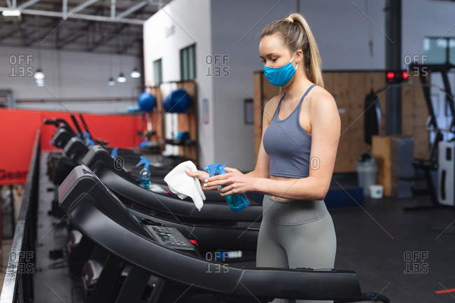 Fit caucasian woman wearing face mask sanitizing cardio machine before working out in the gym.