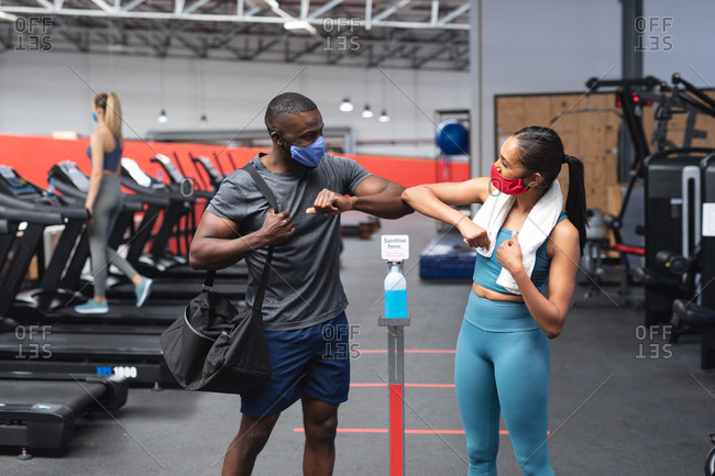 Fit African American man and fit caucasian woman greeting each other by touching elbows in the gym.