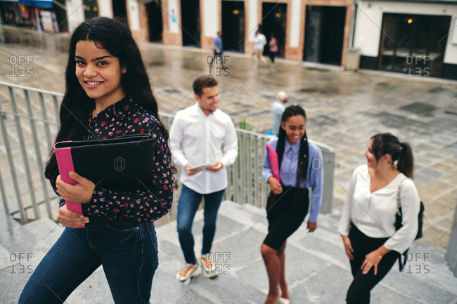From above of young glad female in stylish wear standing on staircase with a folder behind multiracial partners on street and looking at camera