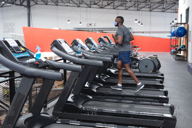 Fit African American man wearing face mask running on treadmill doing cardio workout in the gym.