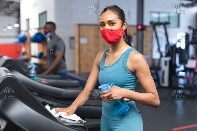 Portrait of fit caucasian woman wearing face mask sanitizing cardio machine before working out in the gym.