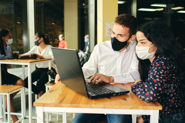 Young unrecognizable smiling friends in face masks surfing internet on netbook at table during coronavirus pandemic
