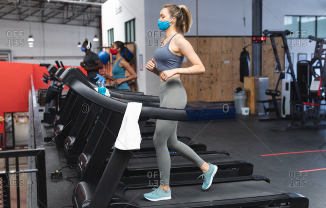 Fit caucasian woman wearing face mask running on treadmill doing cardio workout in the gym.